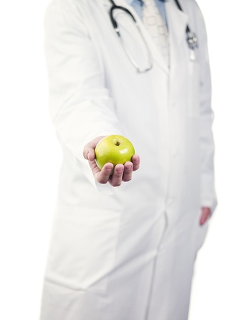 Cropped image of a doctor holding green apple over white background, Model: Derek Gerhardt Stock Photo - 20127478