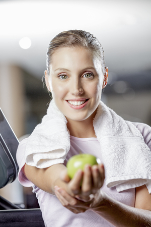 young woman holding an apple while working out Stock Photo