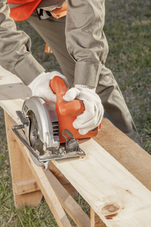 close-up of construction worker hands sawing