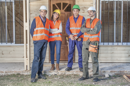 construction crew: 4 person construction crew standing in front of house Stock Photo