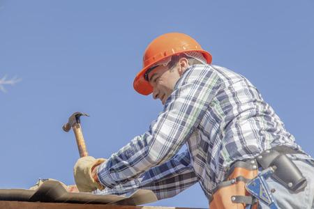 Man working on roof of house Zdjęcie Seryjne