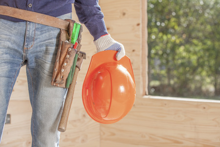 Orange construction helmet and tools on a belt