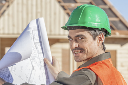 laborer: An orange vested laborer reviewing drawings