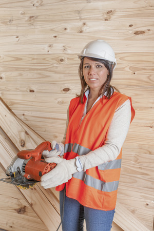 Female construction working with circular saw