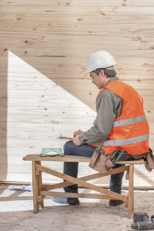 vested: An orange vested laborer holding cordless drill
