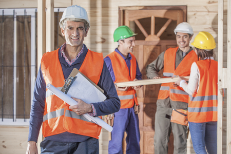 4 person construction crew standing in front of house Stok Fotoğraf