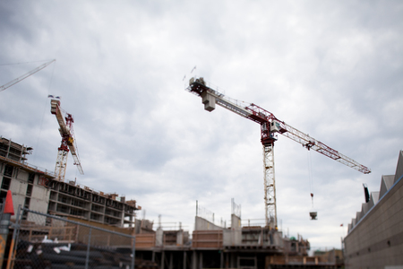 Low angle view of cranes and under constructed building against cloudy sky.