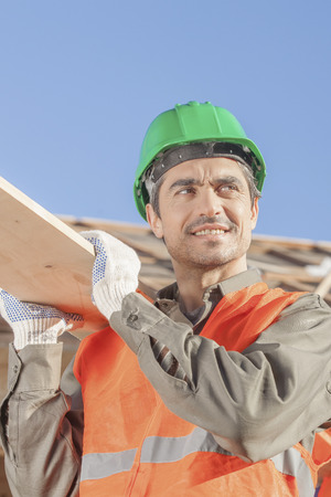 vested: An orange vested laborer helping another carry a board Stock Photo
