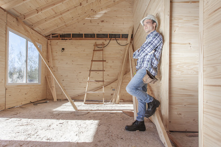 Contractor leaning against wall inside new construction