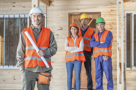 4 person construction crew standing in front of house Foto de archivo