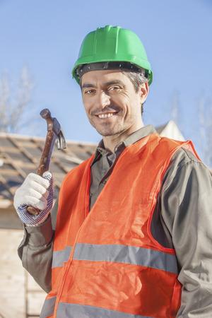 An orange vested laborer holding hammer