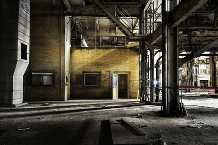 Yellow brick wall outside control room in abandoned industrial coal power station with open door and steel columns
