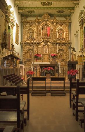 alter: MISSION SAN JUAN CAPISTRANO CHAPEL GOLD ALTER AND CANDLES Stock Photo