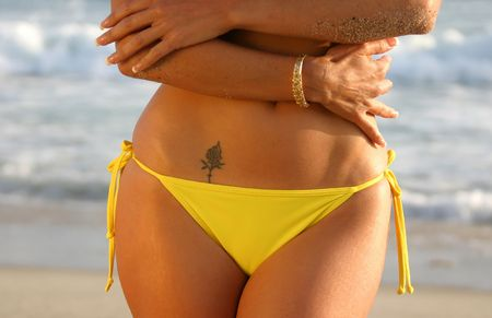 Midriff of a Woman in a Yellow Bikini with a Rose Tattoo on the Beach.