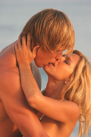 Young Woman holding her Mans face while kissing on the Beach. photo
