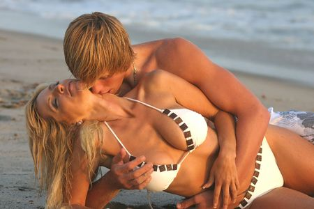 Young couple laying on their sides at the beach embracing with the Man from behind photo