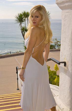 Beautiful Woman Rubio mirando hacia atrás en un blanco backless Viste  Foto de archivo - 2726653