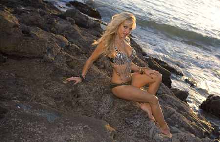 Sexy Woman in flashy outfit posing on the Rocks Stock Photo - 2726658