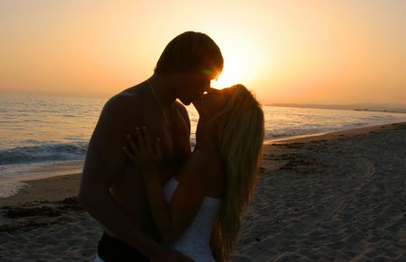 Silhouette Lovers Kissing on tne Beach at Sunset