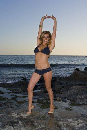 Latina Beauty in Bikini satnding on rocks at the Beach Stock Photo - 2870484