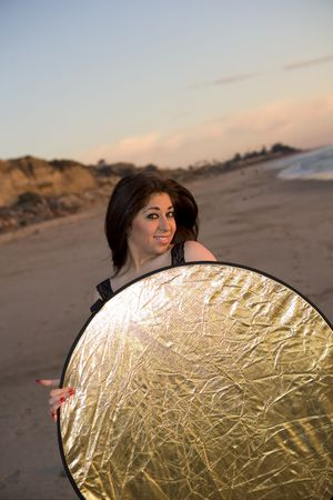 A Brunette Model holding a Reflector at the Beach at Sunset