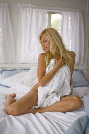 bed sheet:  Woman sitting on bed looking right in her Bedroom Stock Photo