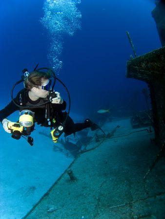 Onderwater Fotograaf kijken naar een gezonken schip met Regulator in haar hand.