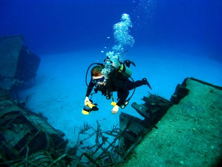 underwater sport: Diver photographing a Sunken Shipwreck in Cayman Brac