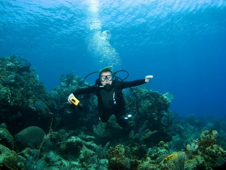 descending: Smiling Scuba Diver descending on a Reef in Cayman Brac Stock Photo