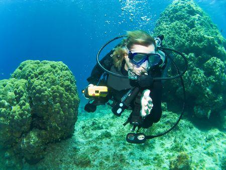Homme Scuba Diver Swimming entre le récif à Cayman Brac