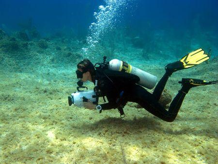 scuba woman: Underwater Videographer shooting on a Cayman Island Reef Stock Photo