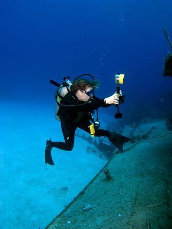 A Female Professional Underwater Photographer schieten de MV Tibbetts in Cayman Brac