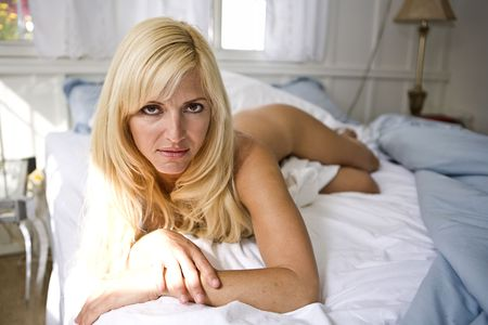 nude blonde woman: Nude Blonde Woman staring into the Camera from her bed Stock Photo
