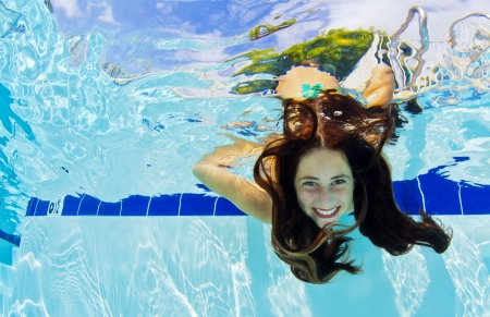 A young girls shows her face underwater photo
