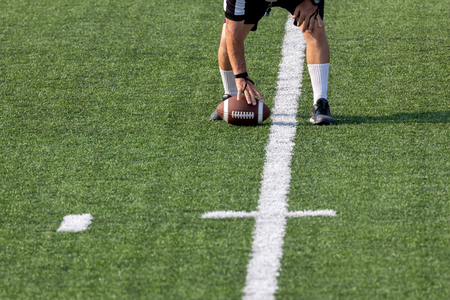American Football Referee placing ball on field for the next play 版權商用圖片