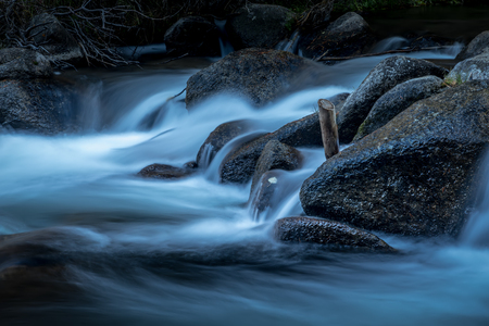 Blue water flowing over rocks in a mountain stream