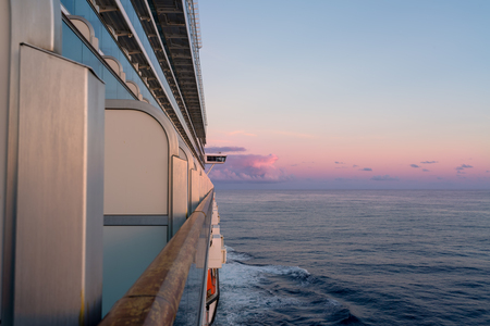 View of the starboard side of a cruise ship at sunset in the Caribbean Sea. Pink skies and ocean in the background