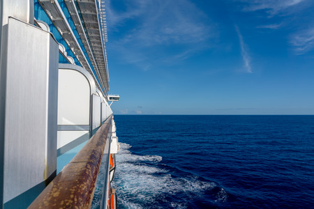 View of the starboard side of a cruise ship on a bright sunny day in the Caribbean Sea. Blue sky and ocean in the background