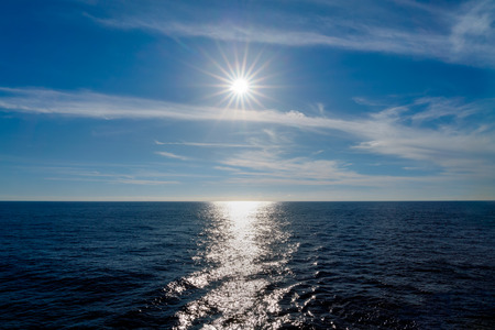 Sun rays reflecting on the Caribbean Sea with blue sky and clouds