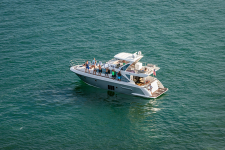 """Port Everglades, Ft. Lauderdale - March 17, 2019: Group of people on pleasure boat hold up """"HAVE FUN"""" sign and wave to the departing Cruise ships. Editorial"""