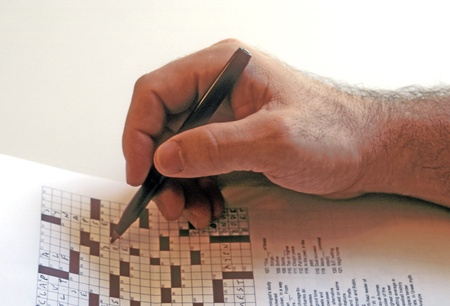 Confident man used ballpoint pen to solve a crossword puzzle.