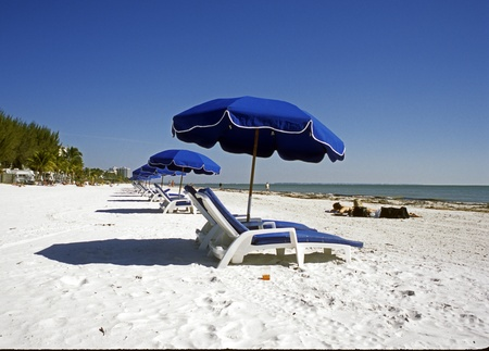 Beautiful sunshine day at Fort Meyers, Florida, beach.  Long row of lounge chairs and blue umbrellas with people in background laying in the white sand and walking the beach. photo