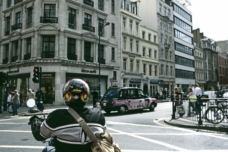 Motorcyclist waits at an intersection on Hanover Street in London, England. Stock Photo - 11298087