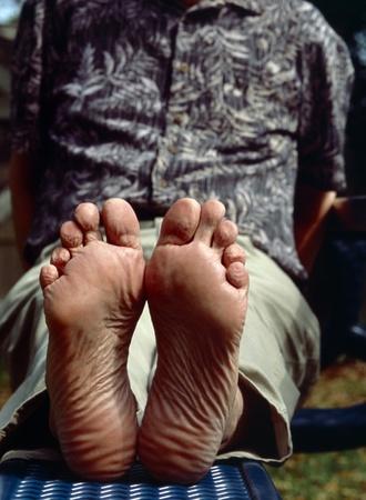 Ein Mann liegt auf einem Aufenthaltsraum mit seinen nackten Füßen auf. Die Sohlen von einem Mann