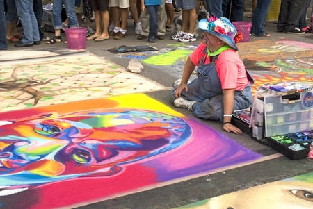 November 4, 2011 - Sarasota, Florida - Artist sits on the street with his box of chalks and drawing as the crowd walks past during the Annual Sarasota  Chalk Festival 2011.