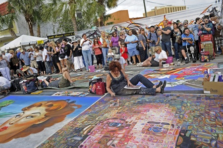 November 6, 2011 - Sarasota, Florida - Two artists sit in the road and finish their chalk drawings as the large crowd watches during the 4th Annual Sarasota Chalk Festival.   Editorial