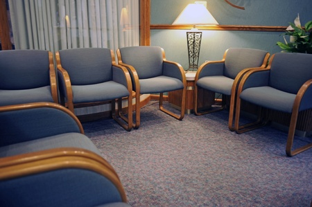 Carpeted waiting room with comfortable chairs and no people. Stock Photo
