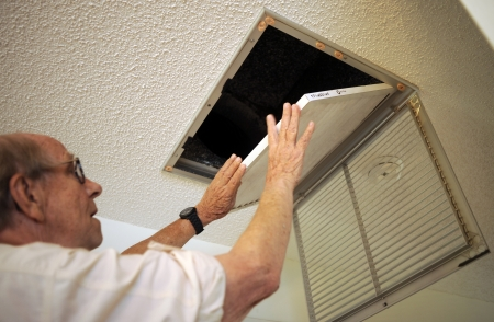 Older homeowner changes the filter in his ceiling airconditioner duct work. Here, he is installing new clean filter.