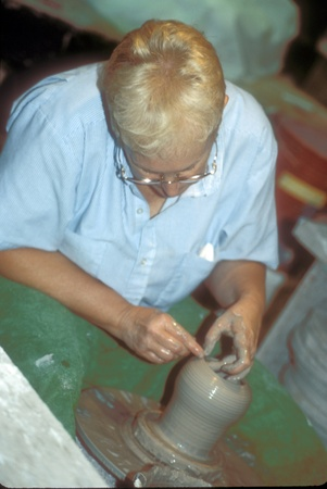 Female potter uses her fingers and spins wet clay into a vase on the potter Editorial