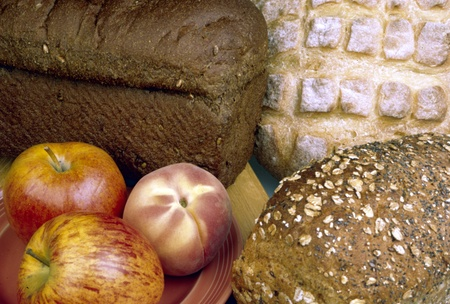 Healthy fruit and bread inccluding apple, peach, rye bread, whole grain bread and sour dough bread. Stock fotó